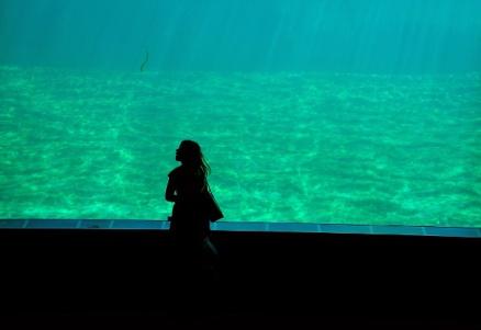 girl walking in front of the underground aquarium
